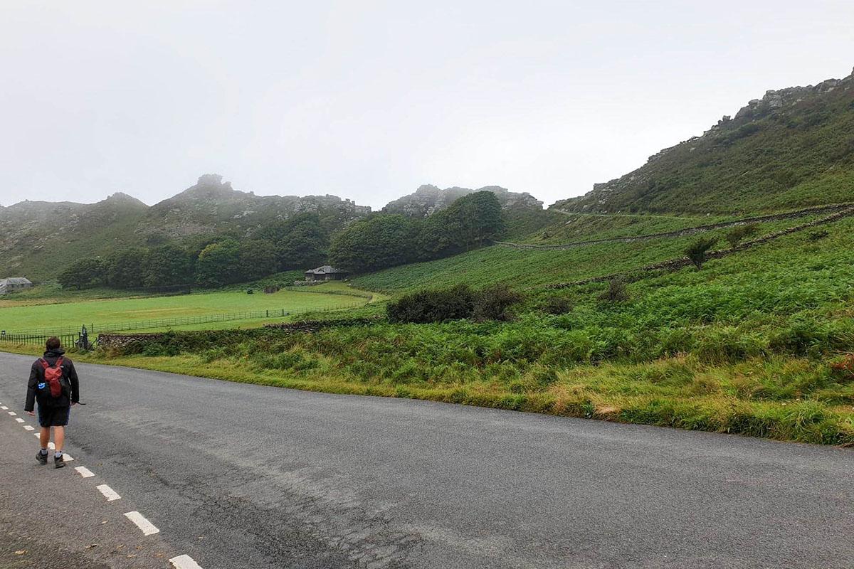 Man walking along road in Exmoor National Park, Devon