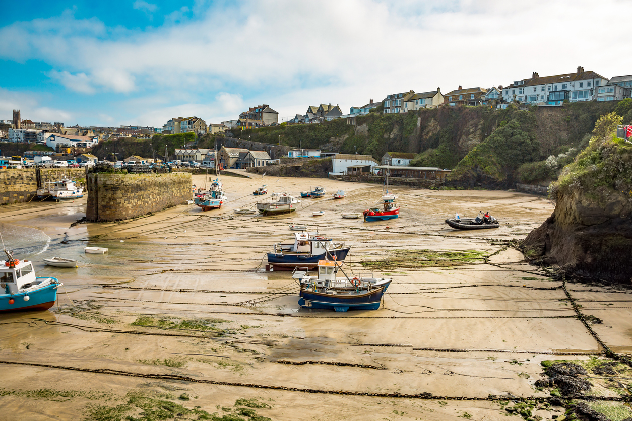 Colorful fishing boats lie at low tide in the harbor of Newquay, Cornwall