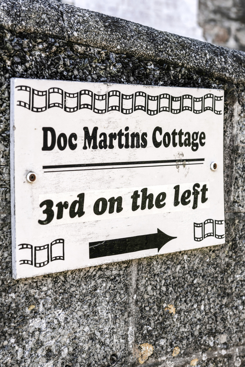 Wall sign pointing to Doc Martin's Cottage in Port Isaac, Cornwall UK