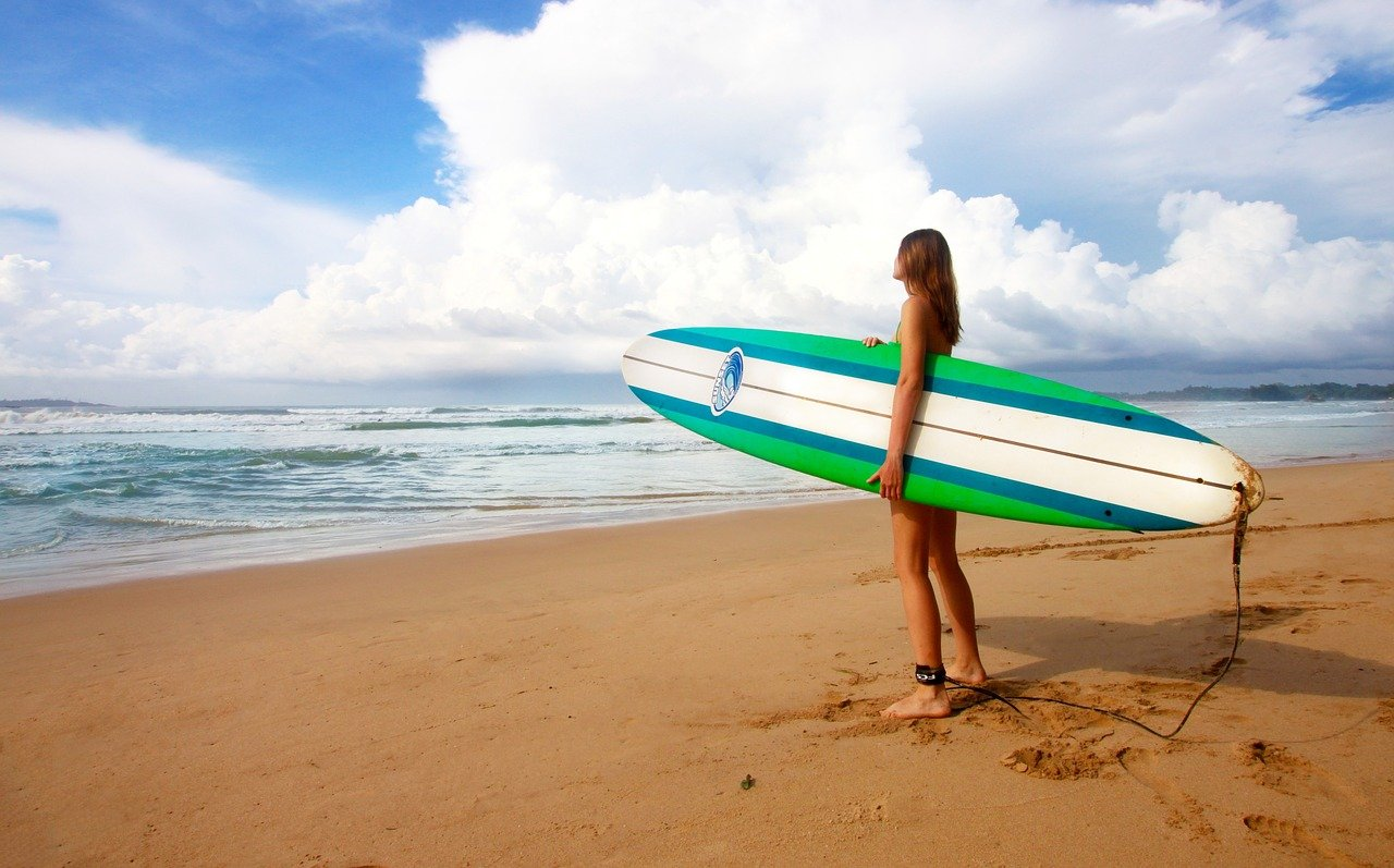 Girl standing on beach with surfboard near St Ives, Cornwall