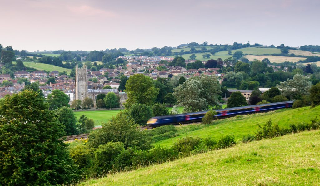 Bruton, England, United Kingdom - July 26, 2012: A First Great Western Intercity 125 high speed passenger train passes the church and town of Bruton, nestled in a valley under the rolling hills of Somerset.