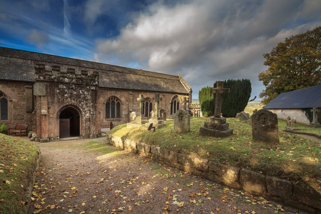 Courtyard of the Anglican Church. You can see old graves. Autumn evening. Clouds in the blue sky. Chagford. Devon. England