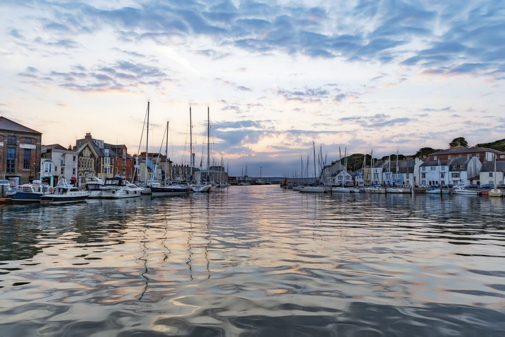Calm waters at Weymouth Harbour at dawn sunrise