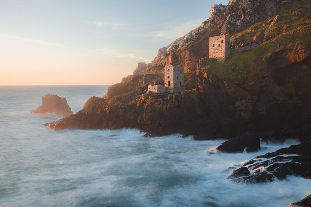 Dramatic seascape landscape of old stone ruins of engine houses at Botallack mines on the Atlantic coast of Cornwall, England, UK during golden hour at sunset or sunrise.