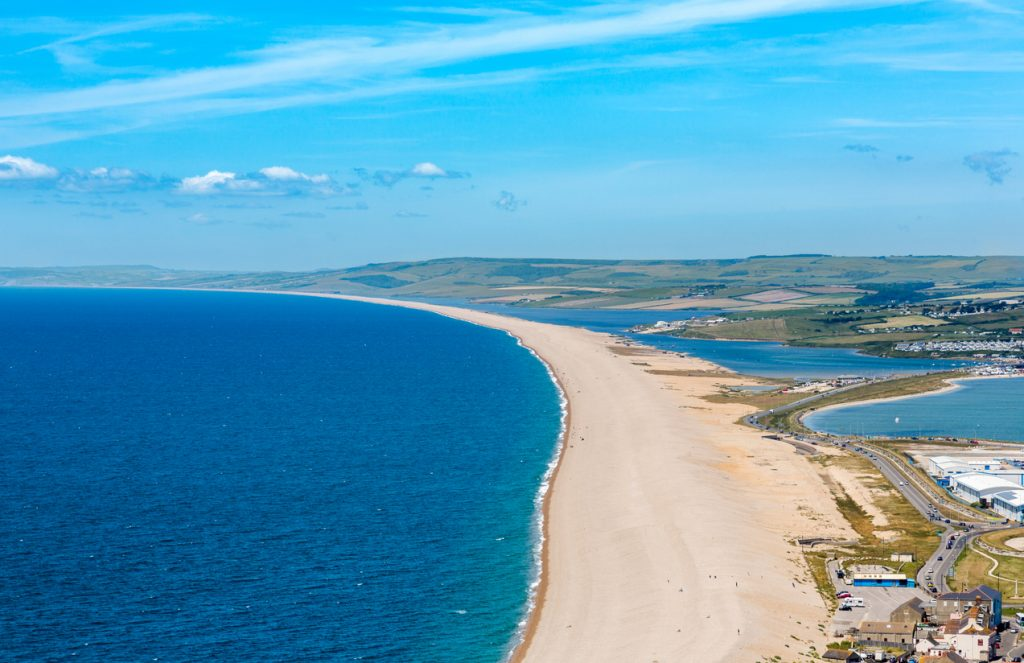 Aerial view on Chesil Beach on Isle of Portland, UK. Horizontal crop, high horizon in sunny summer day, blue sky and azure sea.
